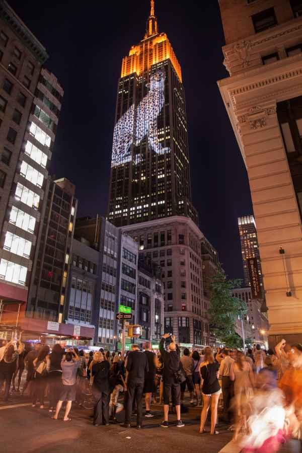 Пешеходы фотографируют проекцию леопарда на Эмпайр Стейт Билдинг в Нью-Йорке